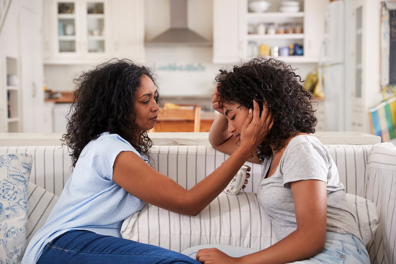 Mother talking to stressed daughter
