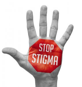 Red sign painted on open hand with words stop stigma